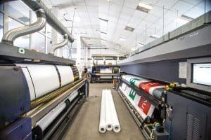Drei grosse Digtaldruckmaschinen in einer Halle
