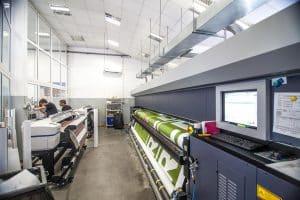 Links zwei Epson Digitaldruckmaschinen rechts eine Große HP Digitaldruckmaschine