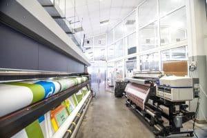 Links eine Große Digitaldruckmaschine und rechts eine kleine Digitaldruckmaschine
