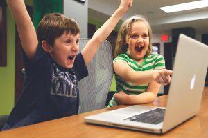 Zwei Kinder sitzen begeistert vor einem Laptop und staunen über unsere guenstigen Banner Preise
