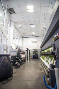 PVC Banner werden auf diversen Maschinen gedruckt, ein Mitarbeiter prüft die Qualitaet