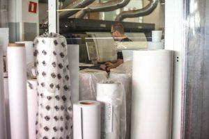 Mitarbeiter sitz am Arbeitsplatz und kontrolliert Daten für Werbebanner, davor steht Bannermaterial