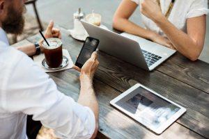 Junge Menschen bestellen Werbeplanen online mit verschiedenen Geraeten